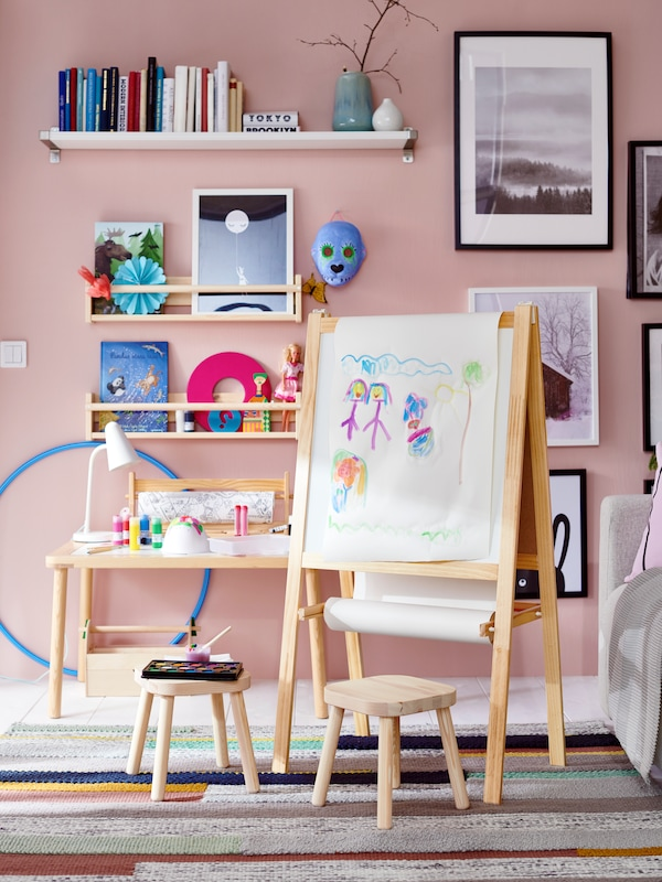 MÅLA easel in a pink bedroom beside a FLISAT children's table and stools. Shelves with books, and pictures are on the wall.