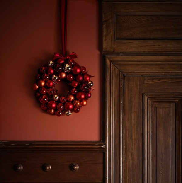 A red wreath of shiny baubles hangs from a red painted wall next to a large dark wooden door with ornate mouldings.