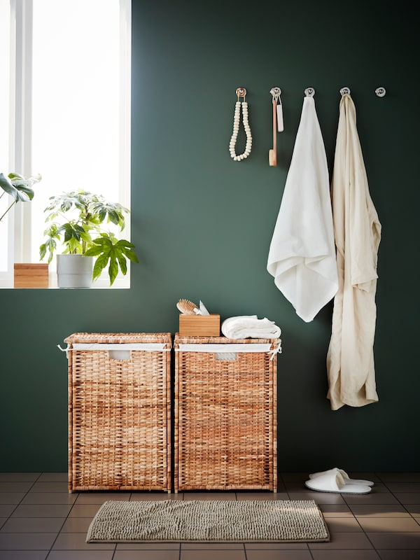 Two BRANÄS laundry baskets by a window with plants, against a green wall with a towel and bathrobe hanging from hooks.