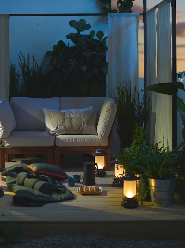 LED lanterns, a blanket, hot dogs and warm drinks under a gazebo on the deck at dusk create a camp-like getaway.