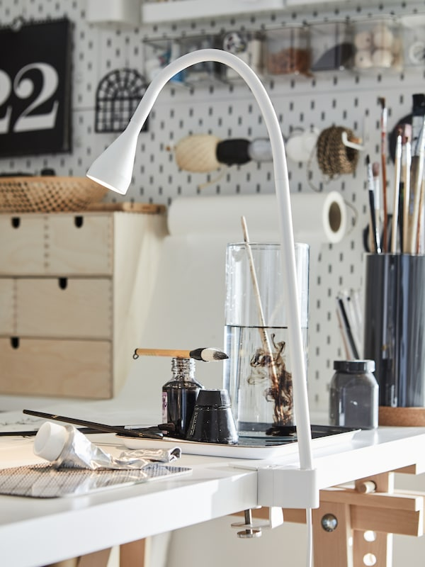 A NÄVLINGE LED wall/clamp spotlight is clamped to a LAGKAPTEN/MITTBACK desk in a hobby area with paints and paintbrushes.