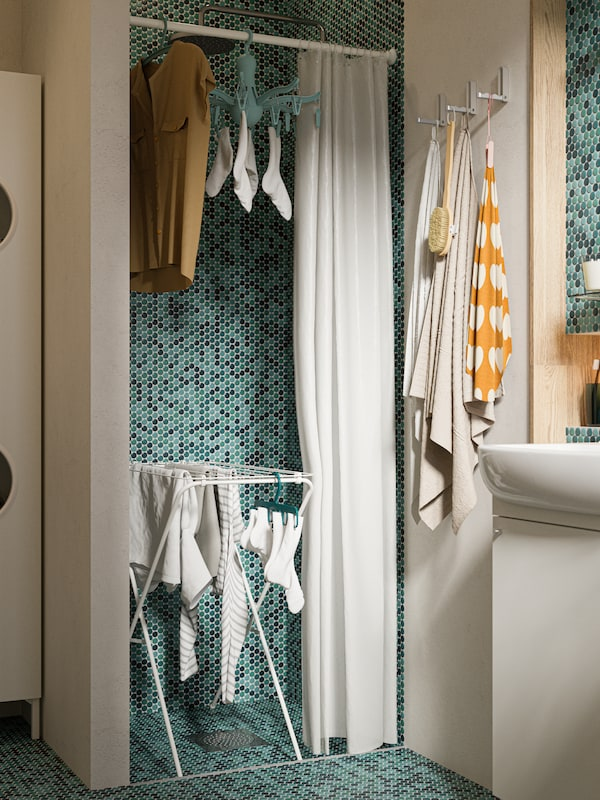 A shower area with green tiles, a drying rack with socks and shirts hanging, a white shower curtain, a shirt on a hanger.
