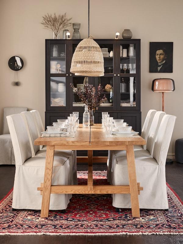 Une longue table en bois avec des verres et de la vaisselle traditionnelle, des suspensions tressées, des chaises revêtues de housses beiges/gris foncé.