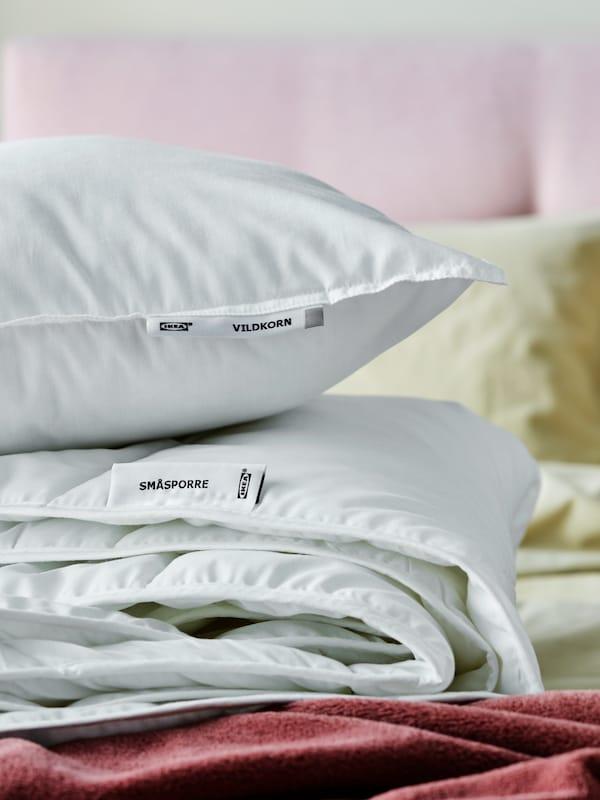 Taiteltu valkoinen SMÅSPORRE-peitto ja VILDKORN-tyyny on aseteltu sängyn päälle. Kuvassa lisäksi TRATTVIVA-päiväpeitto ja ÄNGSLILJA-pussilakanasetti.
