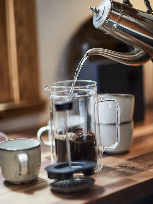 A silver jug pouring water over ground coffee beans in an EGENTLIG coffee/tea maker with GLADELIG mugs to the left and right.