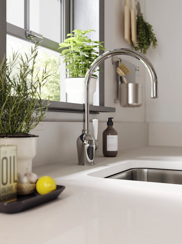 A white kitchen worktop, a chrome-plated kitchen mixer tap, a sink in stainless steel and some herbs by a window.