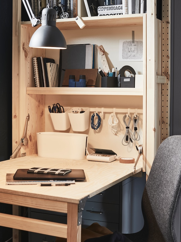 A workspace with an IVAR storage unit with foldable table and books and office stuff on the table and in the shelves.