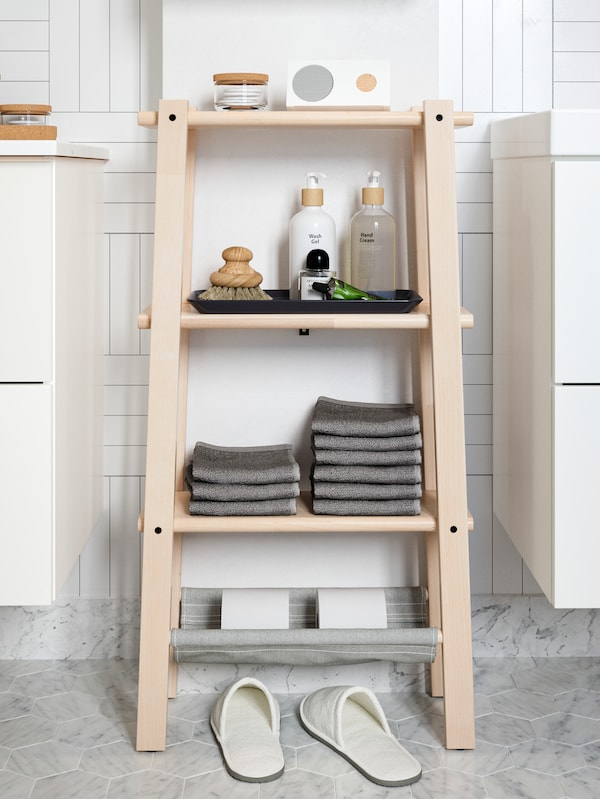A VILTO shelving unit in birch stocked with towels, a speaker and beauty products. A pair of slippers are underneath.