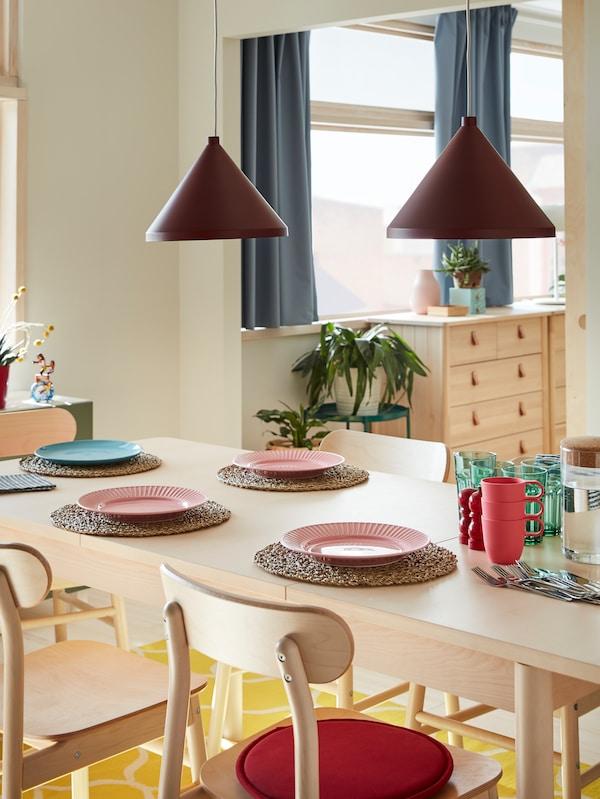 Une table et des chaises en bouleau, un tapis jaune, des assiettes en rose et bleu, des verres verts, des couverts et deux suspensions rouge foncé.