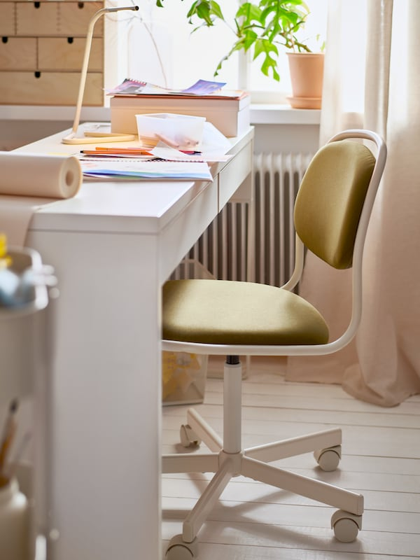 Une chaise pivotante ÖRFJÄLL blanc et jaune-vert, un bureau pour enfant avec une lampe de table, des tiroirs, des crayons et du papier.