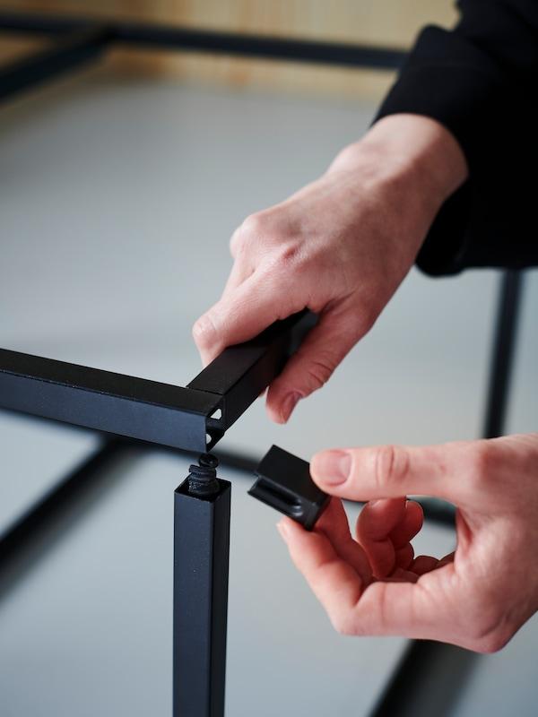 Zwei Hände montieren ein schwarzes ENHET Küchengestell.