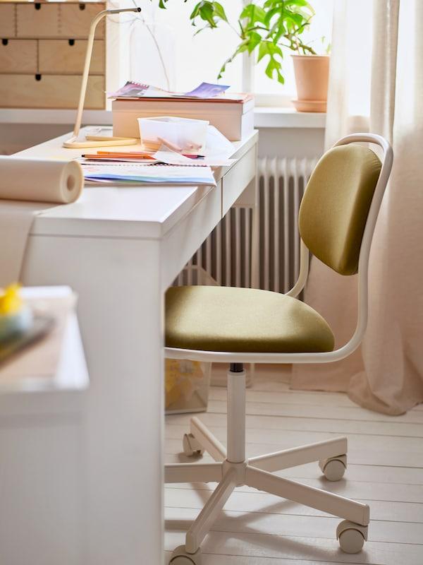 كرسي دوار ÖRFJÄLL أبيض/أصفر-أخضر ومكتب أطفال مع مصباح طاولة ورسومات وأقلام ولفافة ورق منالأعلى.