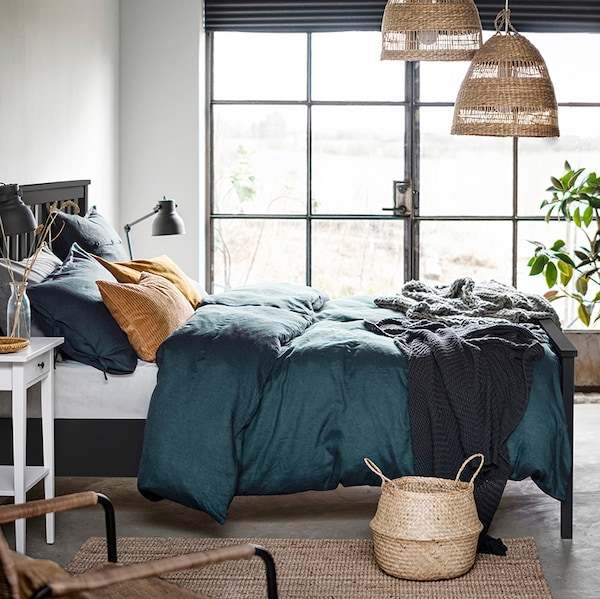 A HEMNES bed stands near a large window under two hanging TORARED pendant lampshades. A FLÅDIS basket sits beside the bed.