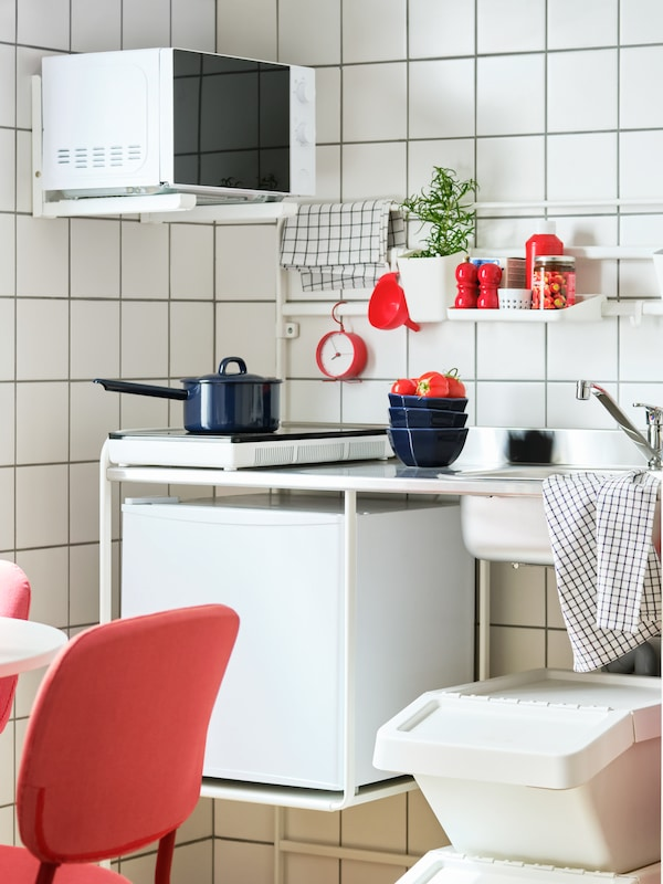 A kitchen with white-tiled walls, a SUNNERSTA mini-kitchen with TILLREDA appliances and a shelf with condiments and herbs.