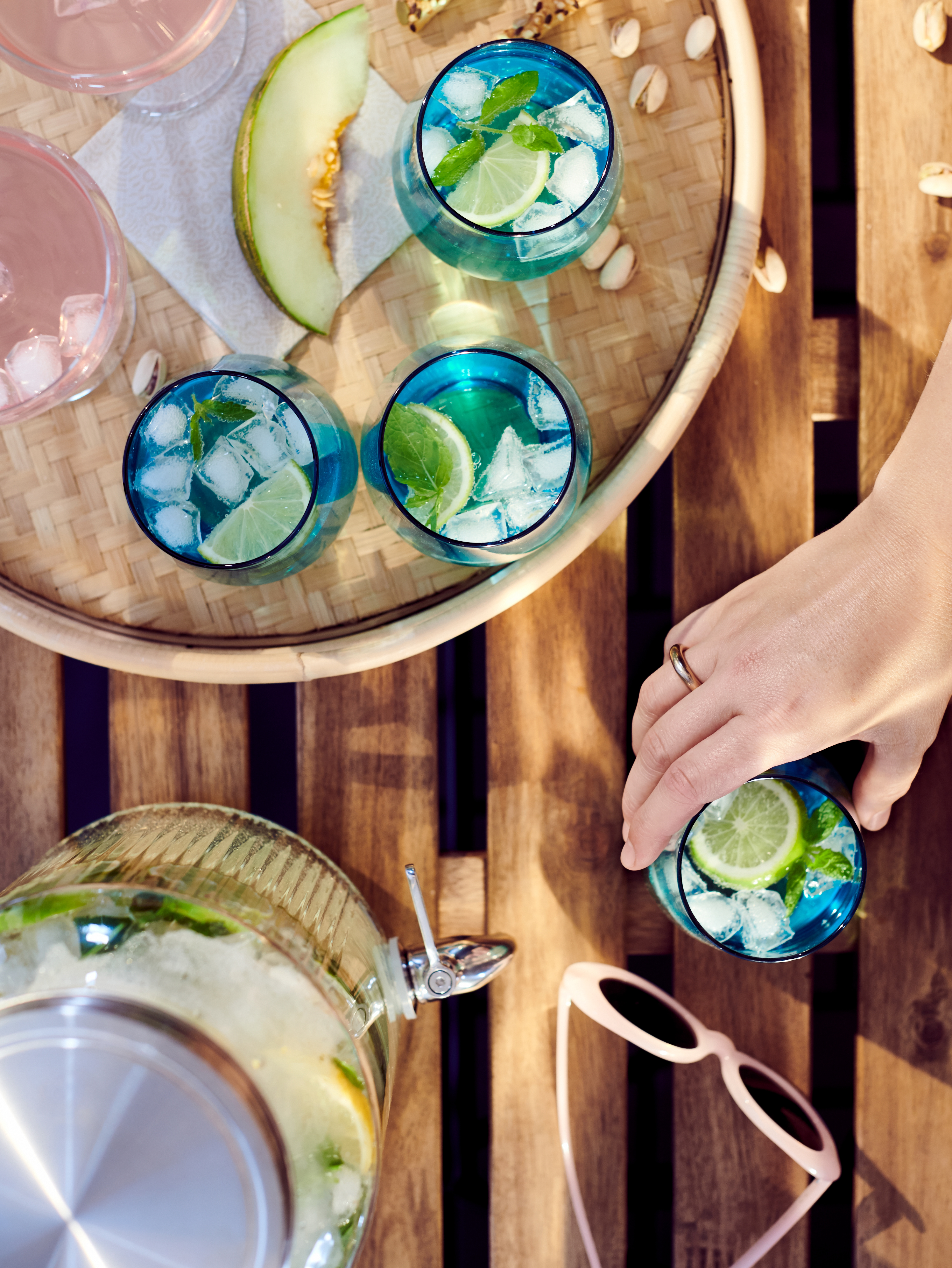 A bird's-eye view of a wooden outdoor tabletop holding a tray and four drinks in blue glasses.