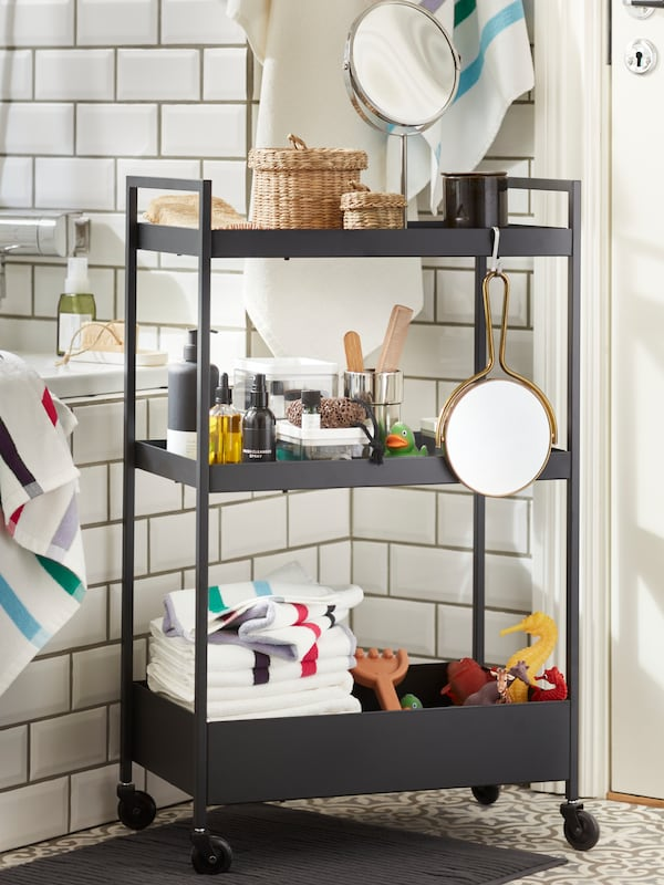 A black NISSAFORS trolley with various items on it stands in a white bathroom.