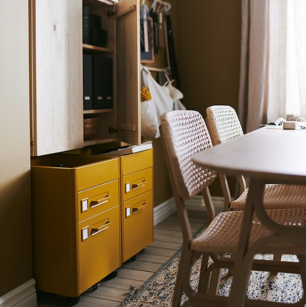 IDÅSEN drawer units on castors in golden-brown add flexible storage to a combined dining and workspace area.