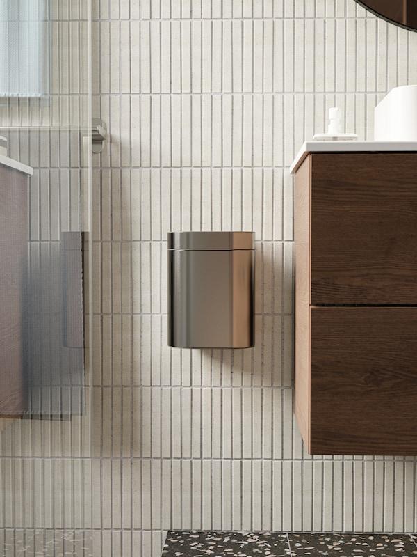 Tong sampah logam dipasang pada dinding berjubin berwarna kuning air di antara kabinet bawah sink dan kawasan pancuran.