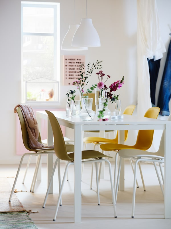 A dining area in white shades with two white MELLTORP tables, white MELODI pendants and different-colour LEIFARNE chairs.