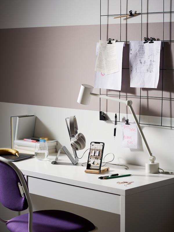 Scrivania con accessori vari posizionati sul piano per organizzare al meglio gli accessori: porta cuffie, porta smartphone, bacheca con clip - IKEA