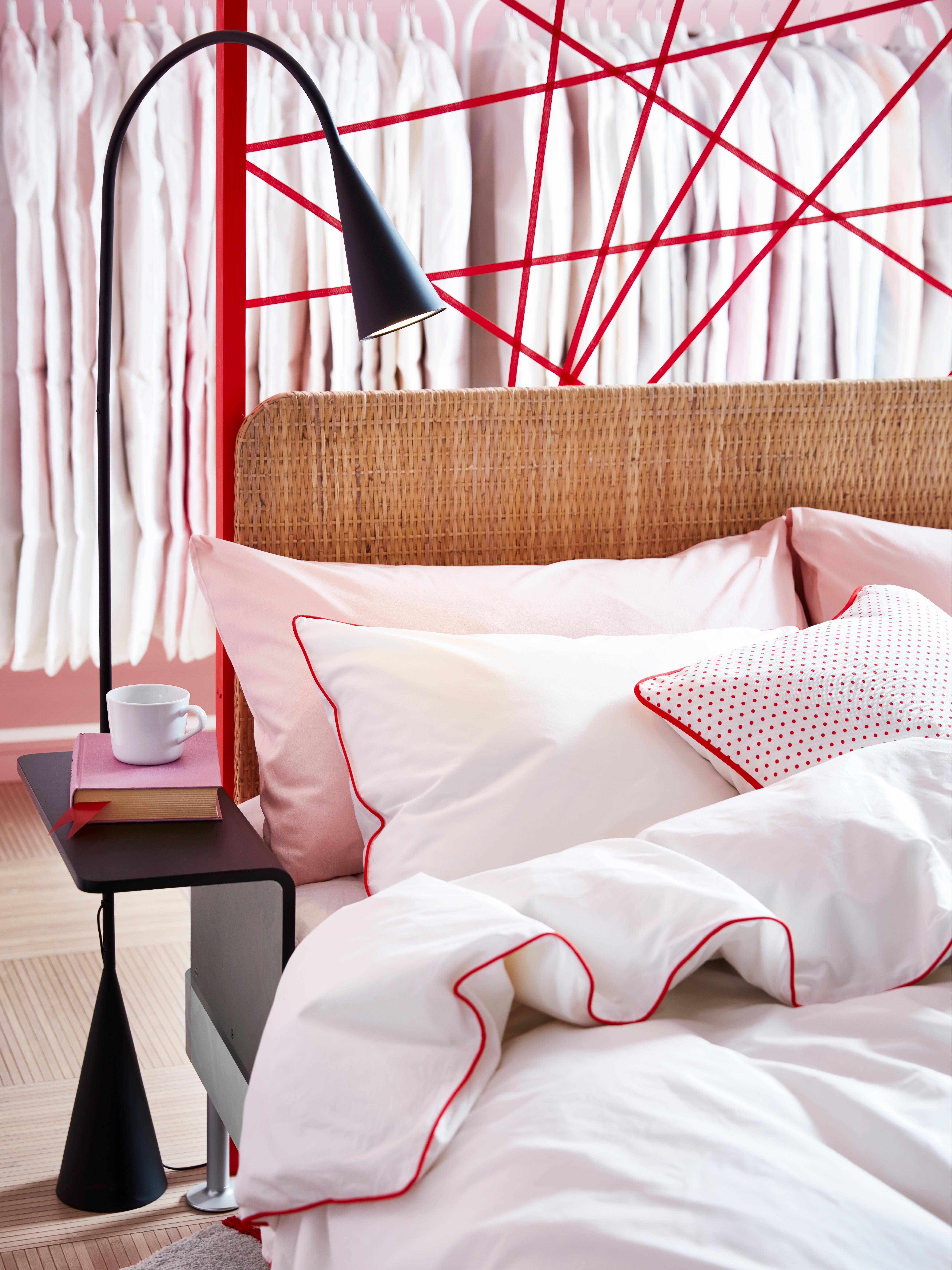 Biancheria da letto bianca su una struttura letto DELAKTIG con testiera in rattan e tavolino con tazza e libro.