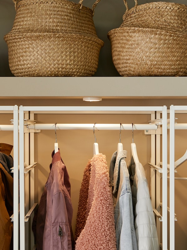 FLÅDIS baskets sit on a shelf inside a built-in wardrobe above a JONAXEL storage combination with hanging clothes.