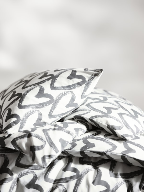 A pillow sits on a roughly folded duvet. Both the pillow and the duvet are inside grey and white LYKTFIBBLA bed linen.
