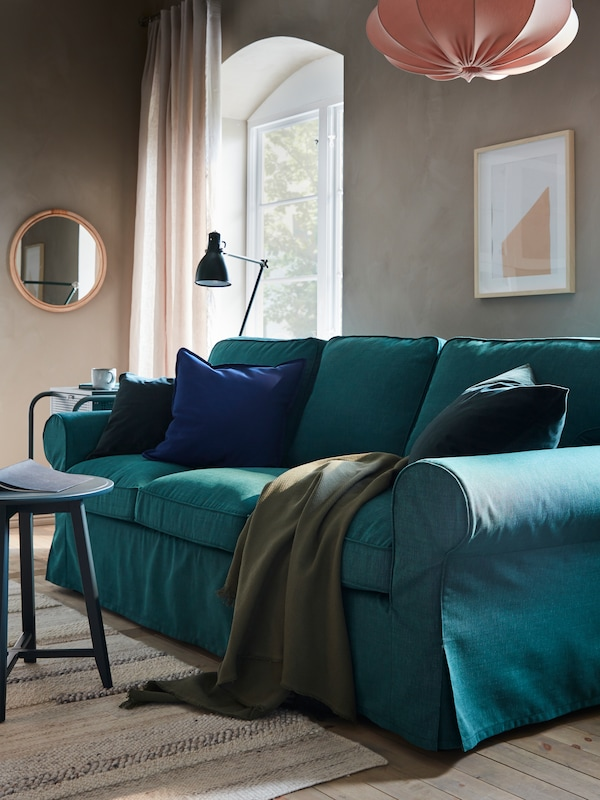 A three-seater sofa in turquoise with a throw laid over it, hanging lamps, and window with curtains and a mirror behind.