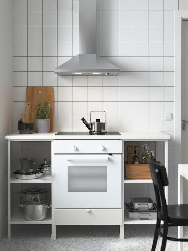 Et hvidt ENHET køkken med gryder, pander og bageplader på hylderne. Ovenover hænger en emhætte i rustfrit stål.