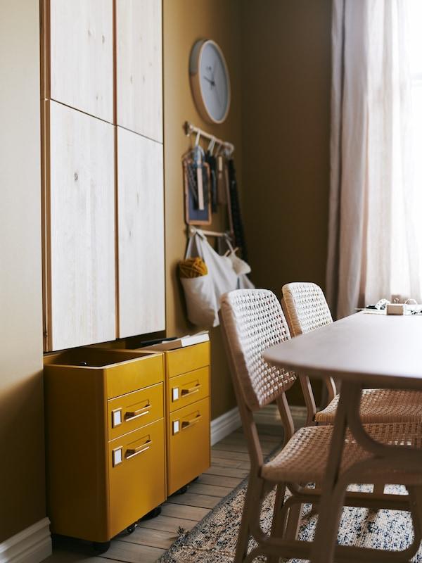 Deux caissons à tiroirs IDÅSEN en brun doré se glissent sous des éléments muraux IVAR en pin grâce à leurs roulettes.