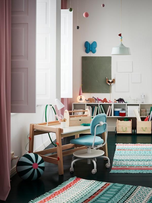 Une chambre d'enfant avec un petit bureau et une chaise dans le style scandinave. Τil y a un espace de rangement à l'arrière du mur avec des livres et des jouets. Au sol, on trouve des tapis et des peluches.