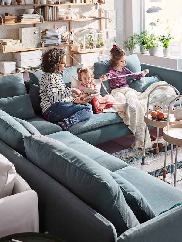 A living room with a family sitting on a SÖDERHAMN sofa in Finnsta turquoise, plants on the window sill.