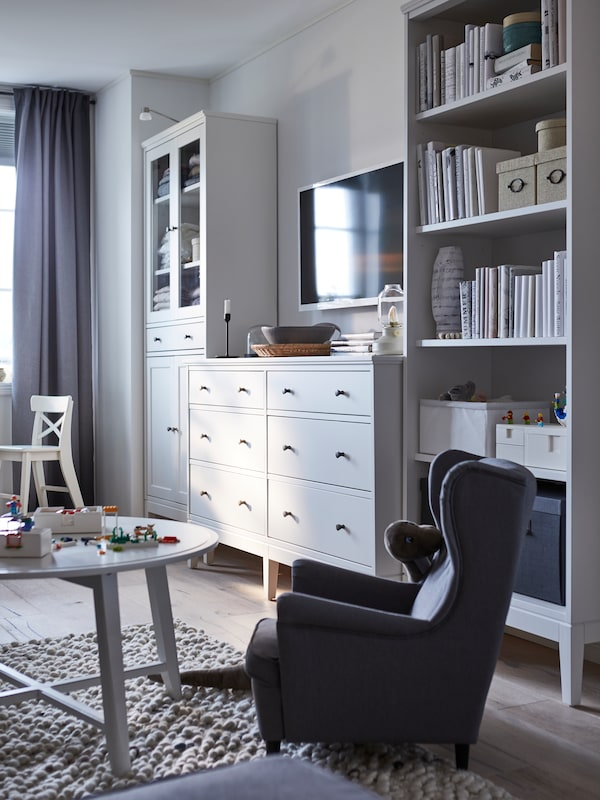 A living room with an IDANÄS glass door cabinet, chest of drawers and bookcase along the wall, by a child's armchair.