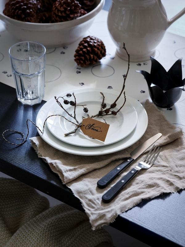 Een gedekte eettafel met twee VARDAGEN borden naast een POKAL glas en bestek. In een schaal en op tafel liggen dennenappels.