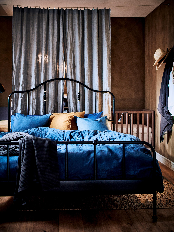 Bračni krevet prekriven plavom PUDERVIVA posteljinom, ispred zavjese izrađene od sive AINA tkanine koja visi duž cijele sobe.
