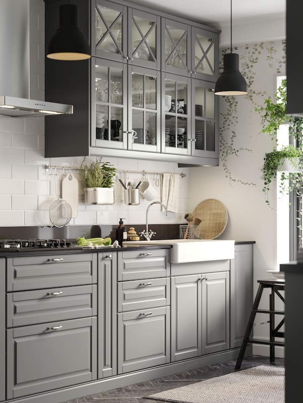 A grey BODBYN kitchen in traditional style with two black HEKTAR pendant lamps. Ivy is growing in the window.