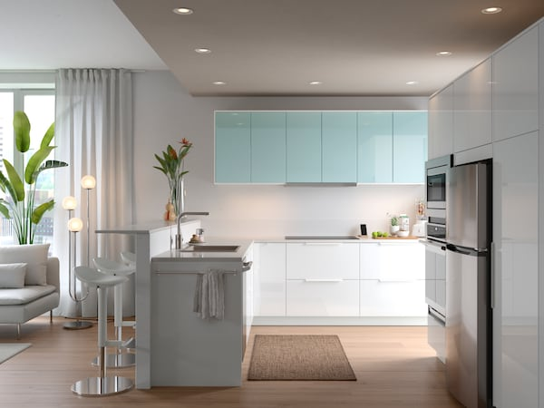A large, bright open-plan kitchen with white and turquoise door fronts and a vase of flowers on the worktop above the sink.