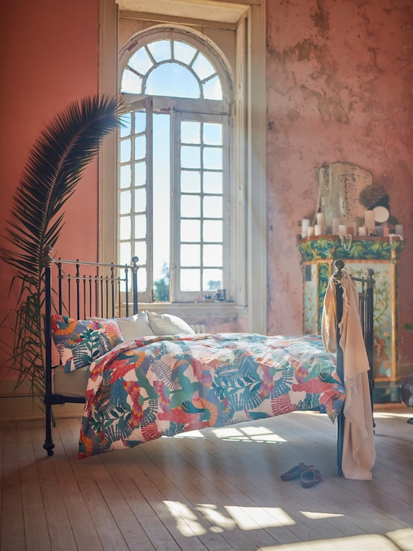 SKOGSFIBBLA quilt cover with a sun-bleached exotic print placed on a bed in a grand room with large windows.