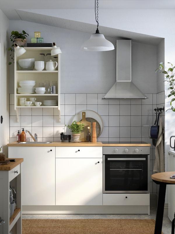 Een keuken met witte tegels en grijze wanden, een witte KNOXHULT keuken met zwarte knoppen en apparaten in roestvrij staal.