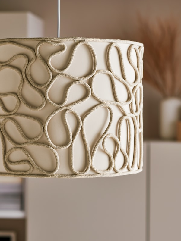 A pendant lamp with a beige VINGMAST lampshade with a curvy rope pattern that winds over a textile-covered inside.