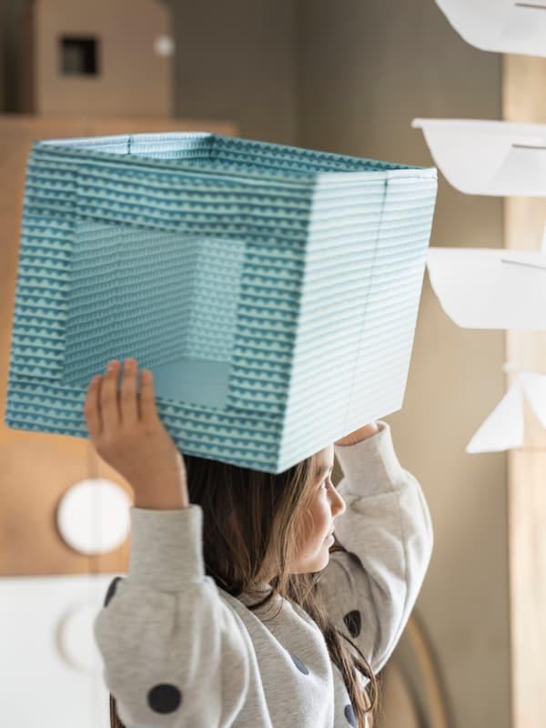 Flicka håller i en UPPRYMD låda över huvudet.