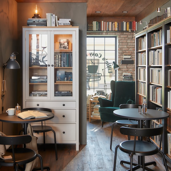 A cafe setting, with bookcases, tables and chairs, a white storage unit with glass doors and books on display.