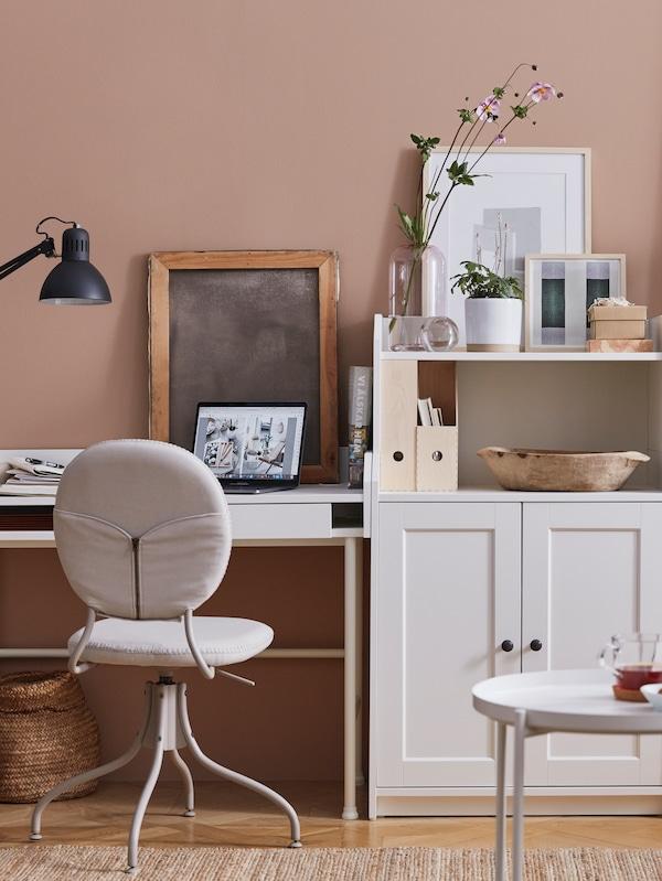 Meja kerja berwarna putih, kerusi pusing berwarna kuning air, komputer riba, kabinet 2 pintu berwarna putih, meja dulang berwarna putih, objek-objek kaca, kerja seni berbingkai.