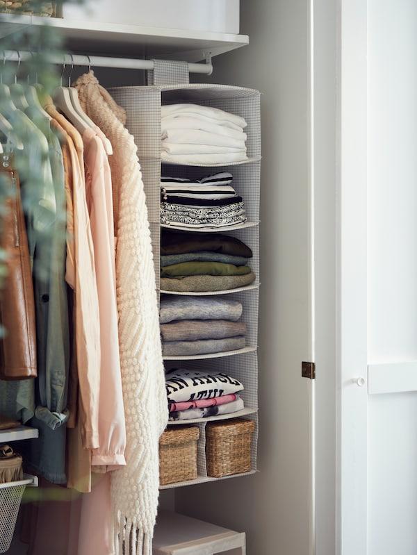 Dans une armoire-penderie, un rangement suspendu à 7 compartiments accueillant des hauts parfaitement pliés, ainsi que des vêtements rangés sur des cintres