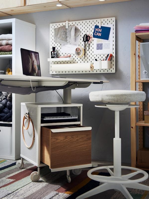 مكتب ووحدة أدراج BEKANT لون أبيض، وداعم للجلوس/الوقوف LIDKULLEN بيج، ولوح تعليق SKÅDIS أبيض ووحدتا رفوف.