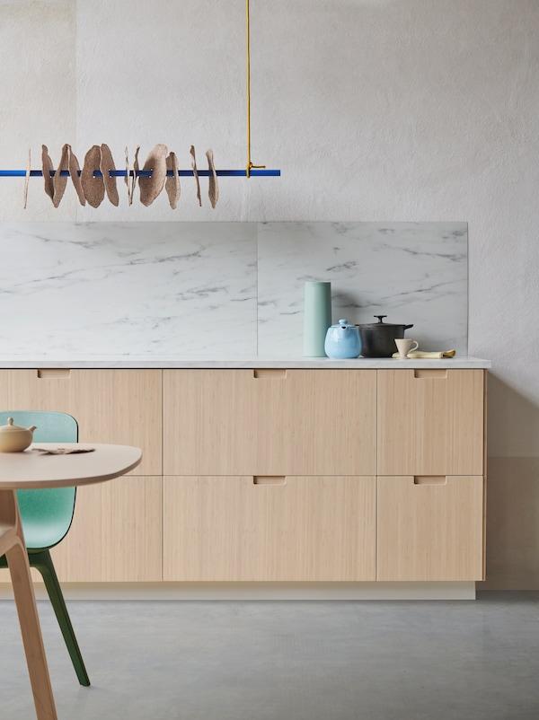Et udsnit af et køkken med fronter lavet af bambus og lysegrå bordplade. Der er tilbehør i blå og mintgrønne nuancer.