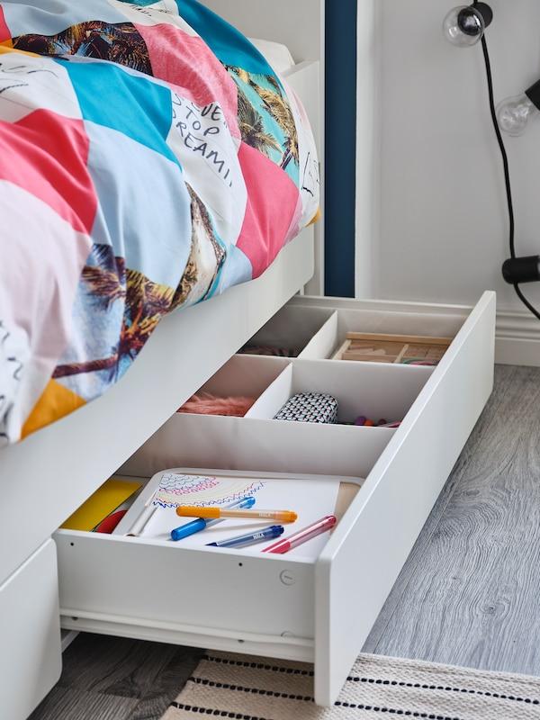Un rangement sous lit est ouvert et révèle des fournitures d'art et d'artisanat.