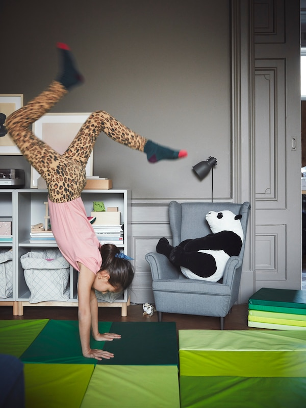 A child doing a handstand on a green PLUFSIG mat in front of a grey STRANDMON children's armchair holding a soft toy panda.