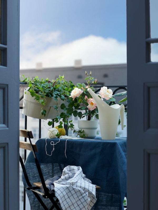 Parvekkeella pieni pöytä, jossa sininen pöytäliina. Pöydällä kastelukannu ja tekokukka. Vieressä parvekkeen kaiteella kukkalaatikko, jossa viherkasveja.