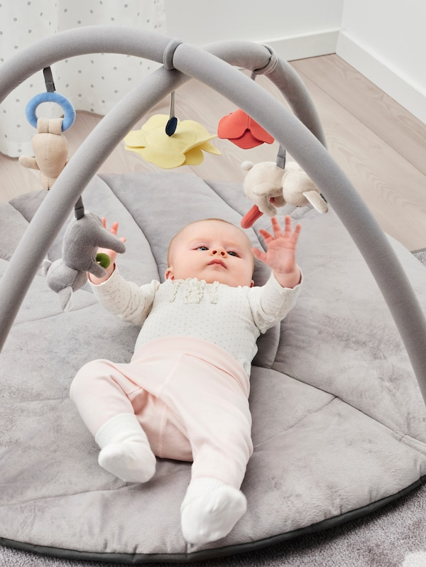 A baby wearing pink trousers and a dotted top lies on its back and plays with the baby toys in a GULLIGAST baby gym.